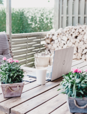 Laptop Outside with Stacked Wood in Background
